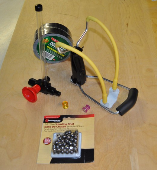 Most of these items are pretty self-explanatory.  The item with a red mouthpiece is a paintball repeater for a blowgun, which we will modify to make the pellet dispenser for the slingshot.