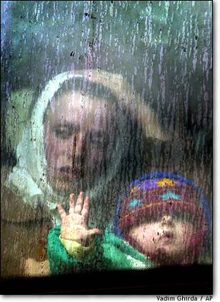7. Mother and child  An ethnic Albanian refugee from Selce, Macedonia, and her child look through the window of a bus as they arrive in Prizren in Kosovo after fleeing the fighting in Macedonia two days earlier.