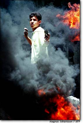 13. Mideast flare-up  A Palestinian youth uses a slingshot to fire stones at Israeli soldiers from behind a barricade of burning tires.