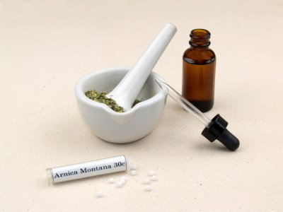 Herbal extraction in an eyedropper bottle, dried herbs in a mortar and Arnica Montana homeopathic medicine.