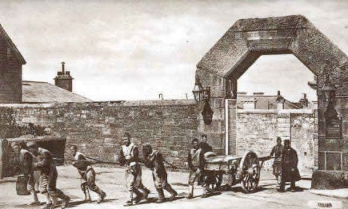 Photo of prisoners at Dartmoor Prison tied together and transporting a cart out the Princetown Gate.