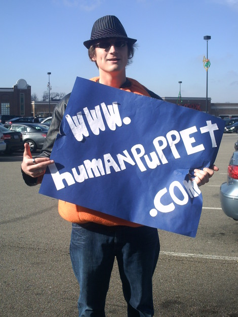 """I first met The Human Puppet while taking photos at the Cincinnati stop of the Sarah Palin book tour. This photo was taken before a police officer explained the """"no signs allowed"""" policy. Behind his sign, he wore a jack-o-lantern costume."""