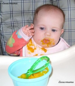 Baby eating mashed pumpkin.
