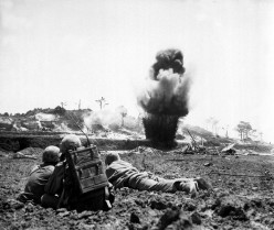 A 6th Division Marine demolition crew watches explosive charges detonate and destroy a Japanese cave, May 1945.