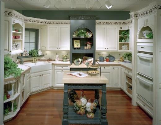 white kitchen cabinets, wood floor, teal walls, island