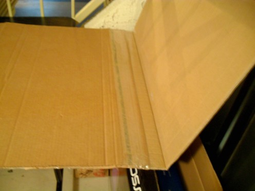 Score the cardboard where it needs to fold and wrap the corners. Be careful not to cut through the cardboard.