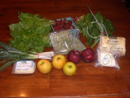 Typical CSA package.  It includes, spinach, lettuce, green onions, garlic scapes, apples, cheese, strawberries and fresh pasta.