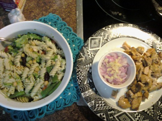 cooled pasta and veggies, with cut chicken, garlic, and red onion