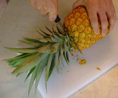 How to cut a pineapple - first top and bottom