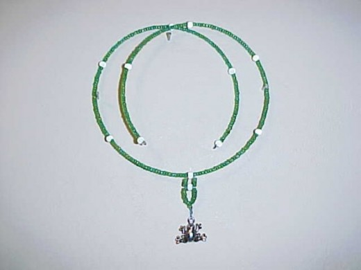 The Charmed Frog-This piece is made with memory wire, green seed beads with a blue hint (glass), glass silver beads, and a pewter frog charm.