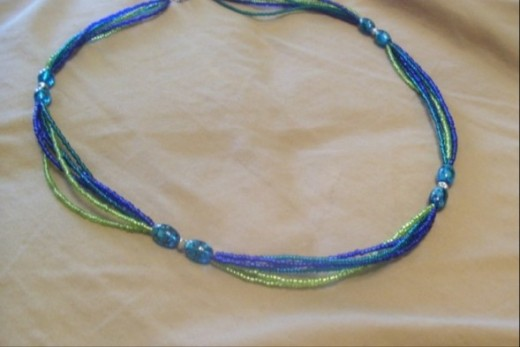 Grace, Calm, and Summer Fun- This necklace is a fun one with glass beads in blues and blue greens, silver bi-cone beads, and seed beads in dark blue, blue green, and lime.