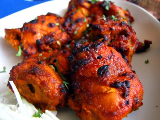 Whole Tandoori chicken cooked in the Tandoor and cut into pieces for serving.