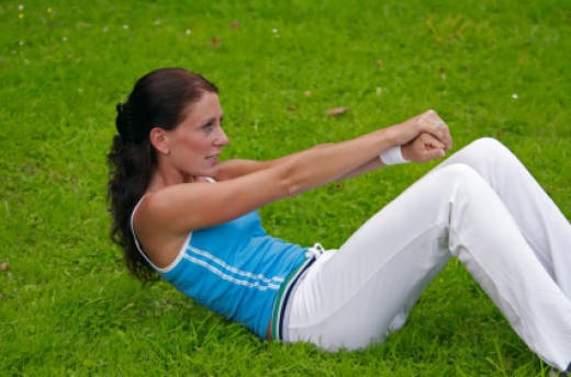 Brunette Girl with Arms Out Straight Performing a Sit Up with a Curved Back to Engage the Abdominal s