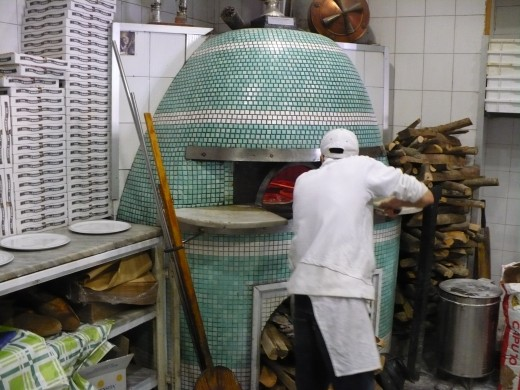 A real pizzaiolo in Napoli placing a pizza into a woodfired oven