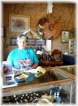 Candy Shores behind a jewelry counter inside of her store