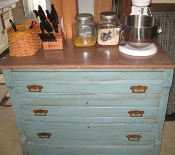Old bureau with marble top serves as counter space and storage for pans