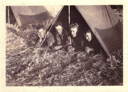 Four soldiers looking very snug in a 2 man army tent.