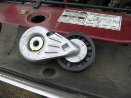 Belt tensioner with hole for ratchet, and decal showing belt routing
