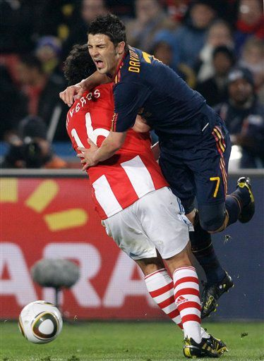 Spain's David Villa, right, is challenged by Paraguay's Cristian Riveros during the World Cup quarterfinal soccer match between Paraguay and Spain at Ellis Park Stadium in Johannesburg, South Africa, Saturday, July 3, 2010. (AP Photo/Ivan Sekretarev)