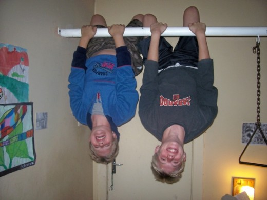 My boys hanging upside down like bats on a pole in my parent's room. The pole extends over my parents' bed and has one or two other items hanging down from it (besides my children) that my father uses to excercise.