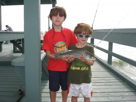 Jonathan and Tristan with a bluefish they caught.
