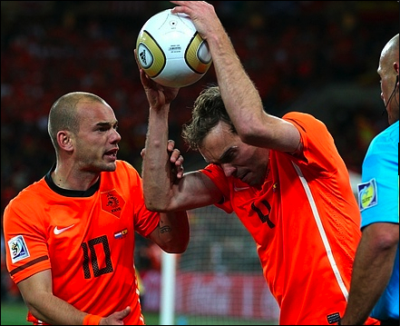 Outraged Netherlands' Joris Mathijsen, right, throws the ball as his teammate Wesley Sneijder tries to stop him after Spain's Andres Iniesta scored the winning goal.