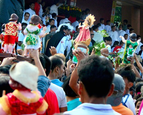 People raise their images of the Santo Nino for the blessing
