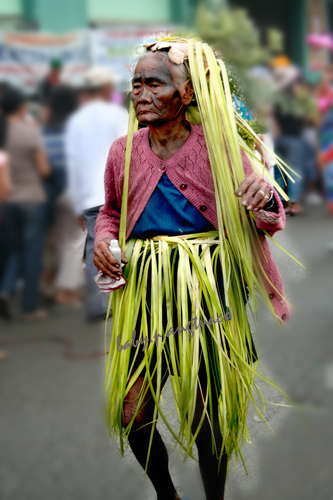Old lady using coconut leaves for her costume