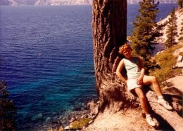 My niece resting against a tree trunk on the steep hike down to Crater Lake