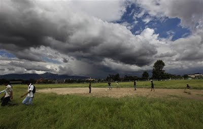 Boys play with a soccer ball on ground overgrown with weeds as monsoon clouds hover over, Kathmandu, 8/27/09 (AP/Gemunu Amarasinghe).