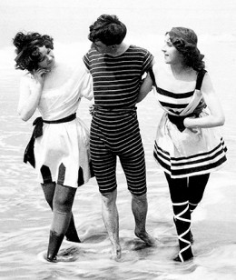 Trollops vamping a naive man as they stroll on the beach.