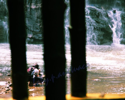a photographer framed by some posts in the foreground as he tried to get a shot of the waterfalls in the background