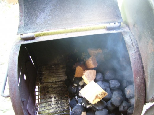 Charcoal fire with mesquite wood chunks on top for smoke
