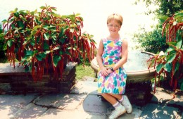 My niece sitting between urns of Chenille plants at Bellingrath Gardens