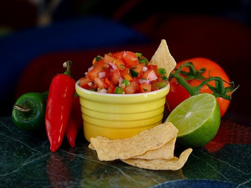 A bowl of fresh salsa, surrounding by some of the ingredients used to make it.