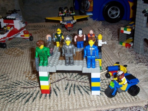 Lego people standing at attention on platform surrounded by lego vehicles. Legos encourage imaginative play.
