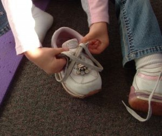A girl learning to tie her shoe. Image by Tory Byrne, Stock.xchng