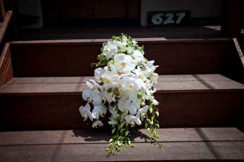 Large white orchids, dendobrium, white roess, stephanotis and pittoporum make up this beautiful bouquet.