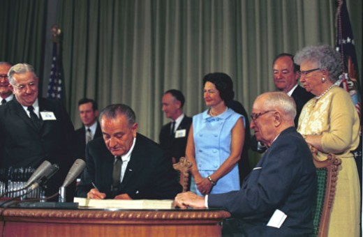 President Johnson signing Medicare and Medicaid into law