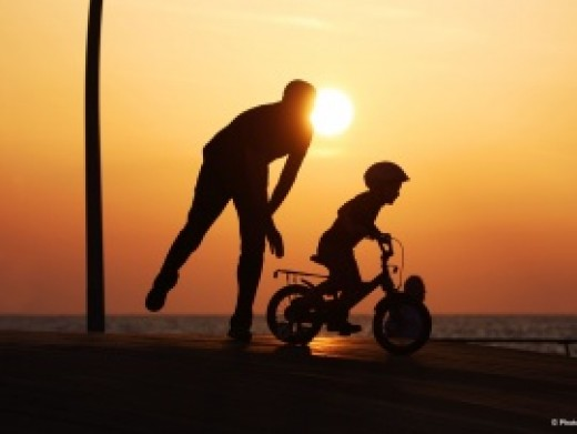 Dad pushing son on bicycle at the beach   Courtesy of www.Photo8.com