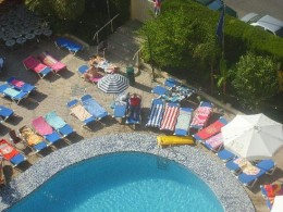 view of towel-covered but empty sunbeds round the pool