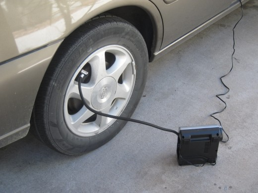 Inflating automobile tire using a small portable tire inflator using car cigarette lighter as power source
