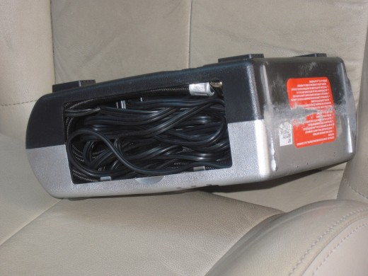 Air Hose and power cord on portable Auto Tire Inflator fold into compartment at bottom of unit.