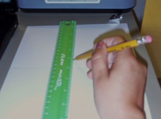 Use the ruler to score the card stock in half by the height.
