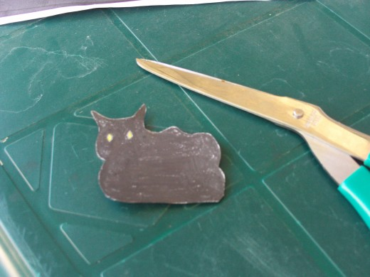 Use scissors to cut out the picture of the Halloween cat.