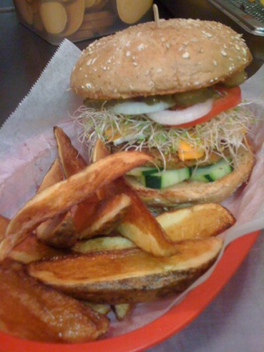 Homemade vege patty topped with Follow-Your-Heart cheddar & mozzarella, sprouts, cucumber, tomatoes, pickles, onions, &veganaise.