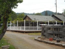 This building was once a restaurant. The white fence encloses a spacious deck.