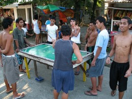 Typical Filipino makeshift billiards table being used outdoors. Filipino males wear shorts and go sleeveless or shirtless because of the hot and humid weather.