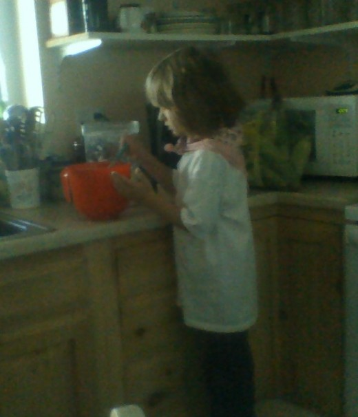A child whisking together the pancake batter at the counter