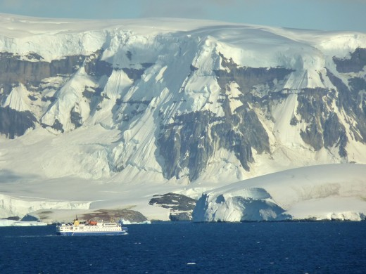 A small cruise ship is dwarfed beside the Antarctica penninsula